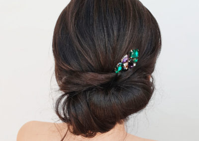 softly textred chignong hair style featuring dark brunette hair with a Lovisa emerald and purple hair accessory