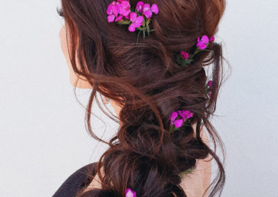 pink posies styled in a long warm brunette braided hair style for a wedding