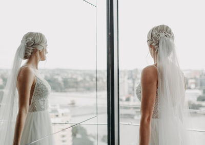 platinum blonde bridal upstyle in a beautiful twist design. Bride looking out to Brisbane river, dressed in her wedding dress, veil and boquet in hand