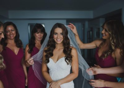 Brunette bride surrounded by bridesmaids fixing her veil